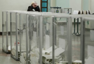 An observer waits for the start of ballot counting at a polling station after voting day in Kiev