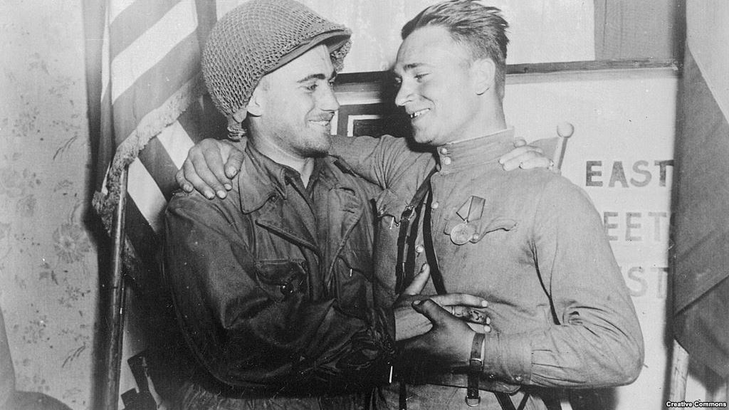 Лейтенанты У. Робертсон и А.С.Сильвашко на фоне надписи «Восток встречается с Западом», символизирующей историческую встречу союзников на Эльбе 25 апреля 1945 г.